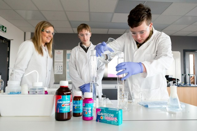 "Students Brad Lawrence, 14, front, and Alex Bailey, both 14, take part in a demonstration of the science behind RB's Gaviscon ""powerbrand"", supervised by Annabel O'Fee, RB R&D Associate."